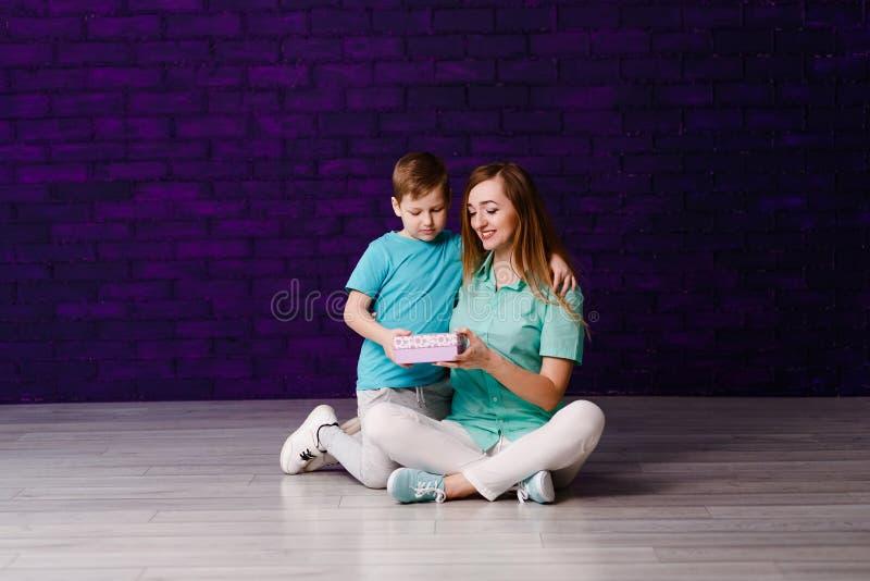Семилетний мальчик и усмехаясь 30-год-старая женщина раскрыть подарочную коробку совместно пока сидящ на поле стоковые изображения