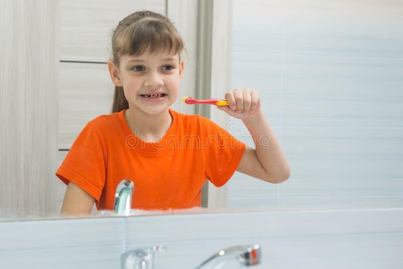 Семилетняя девушка смотрит себя в зеркале перед чистить ее зубы щеткой стоковые изображения rf