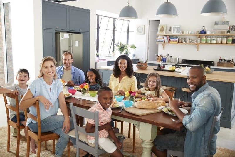 2 семьи имея обед совместно дома смотря к камере стоковые фото