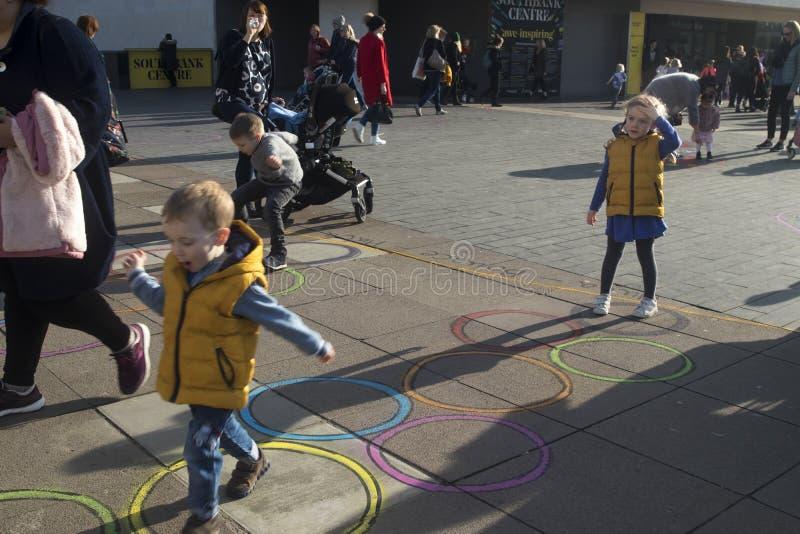 Семьи с детьми играя на установке искусства вне королевского фестиваля Hall в южном береге стоковое изображение