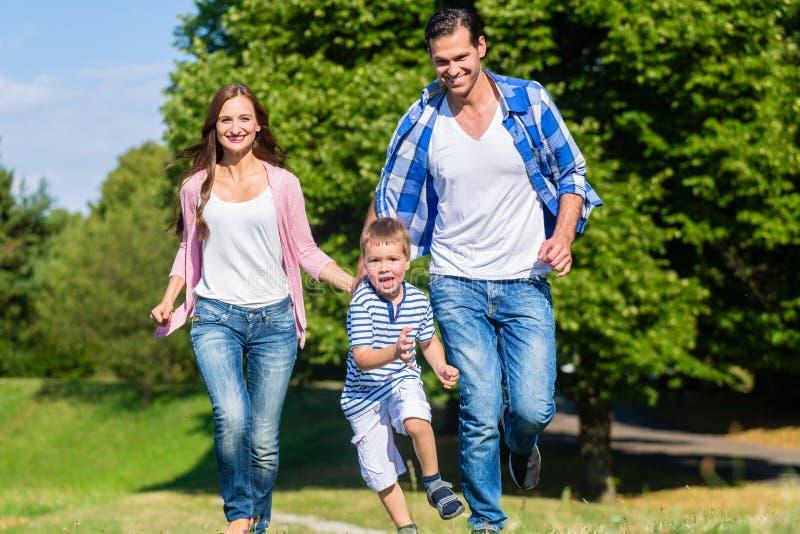 Семья бежать быстро в траве на луге стоковые фотографии rf