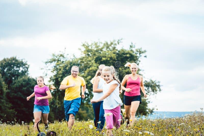 Семья бежать на луге для спорта стоковая фотография rf