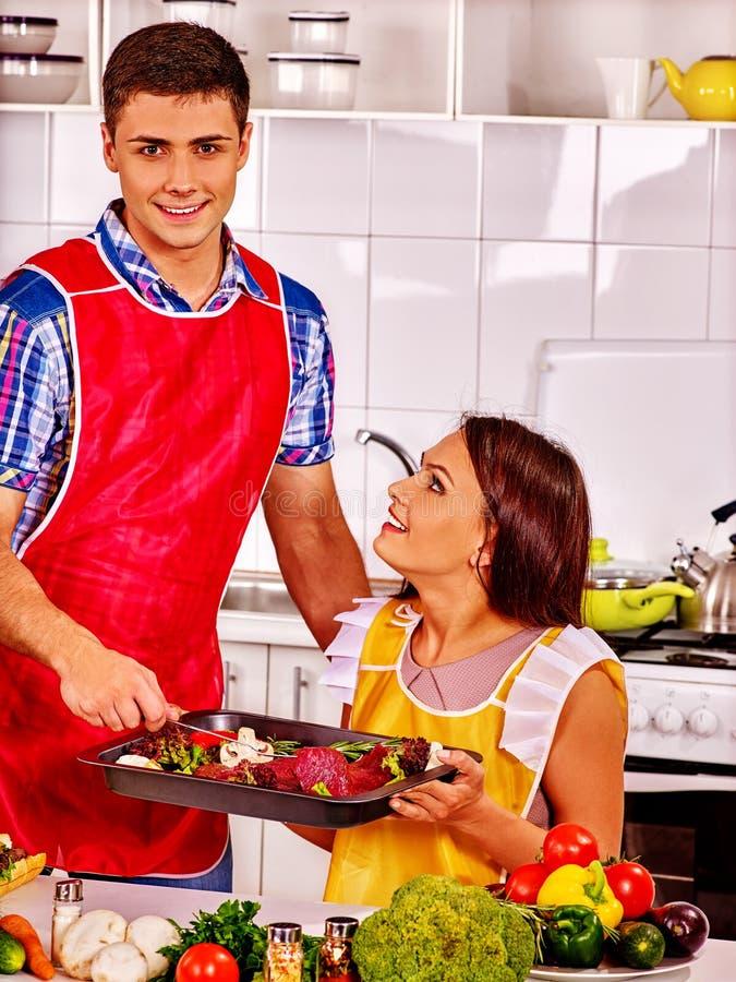 Семья варя мясо на кухне стоковые фотографии rf