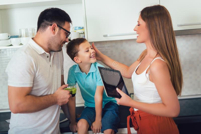 Семья в кухне используя цифровой планшет стоковая фотография