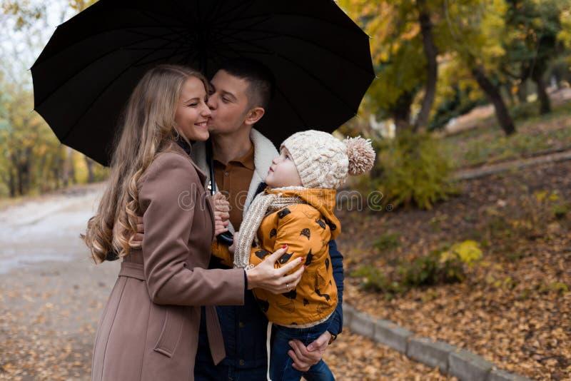 Семья в осени в зонтике дождя леса стоковое изображение