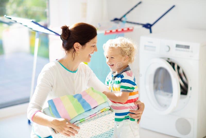 Семья в прачечной со стиральной машиной стоковое изображение