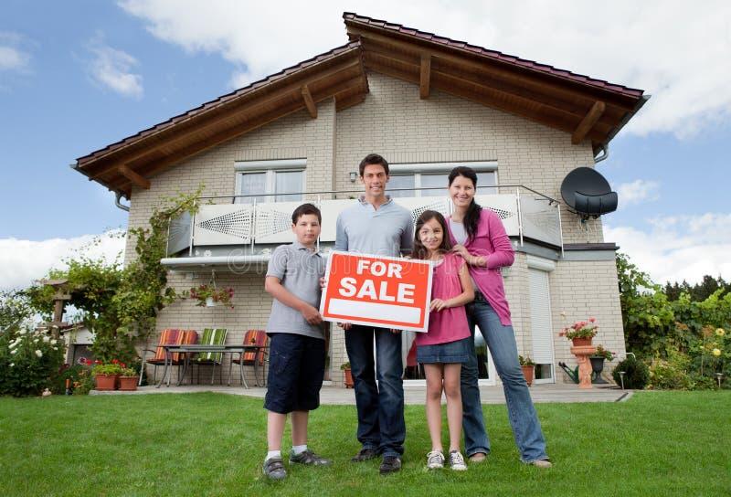 семья держа домашнее сбывание продающ знак их стоковое фото rf