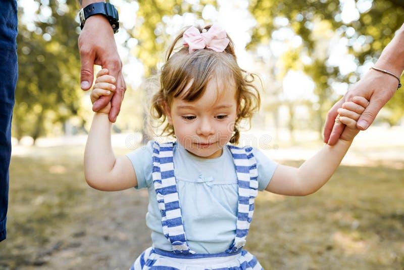 Семья держа руки, приемный ребенка будучи поддерживанным путем любя родители стоковое фото