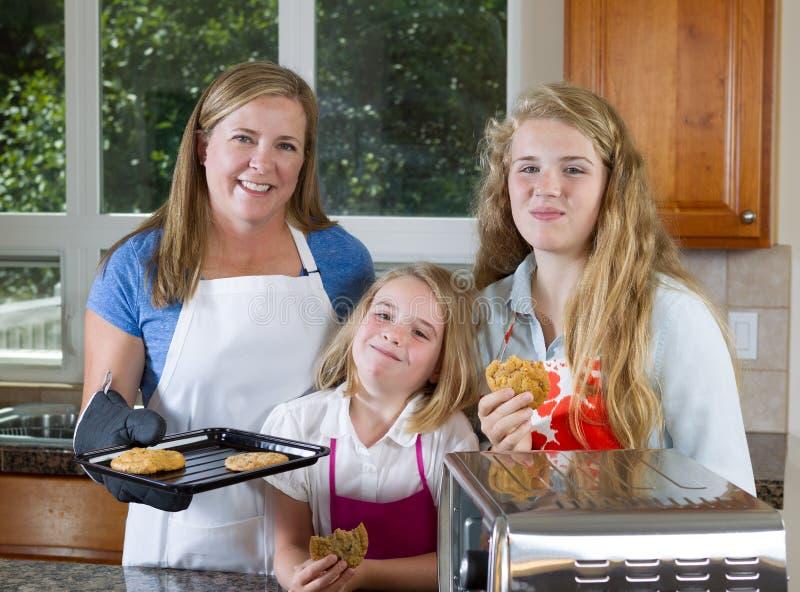 Семья девушек еды свеже испеченных печений стоковое фото rf