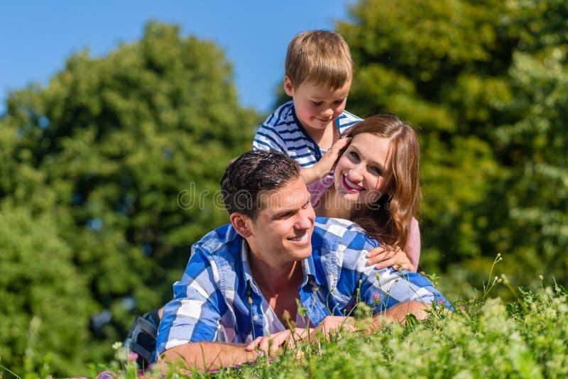 Семья лежа в траве na górze одина другого стоковые фотографии rf