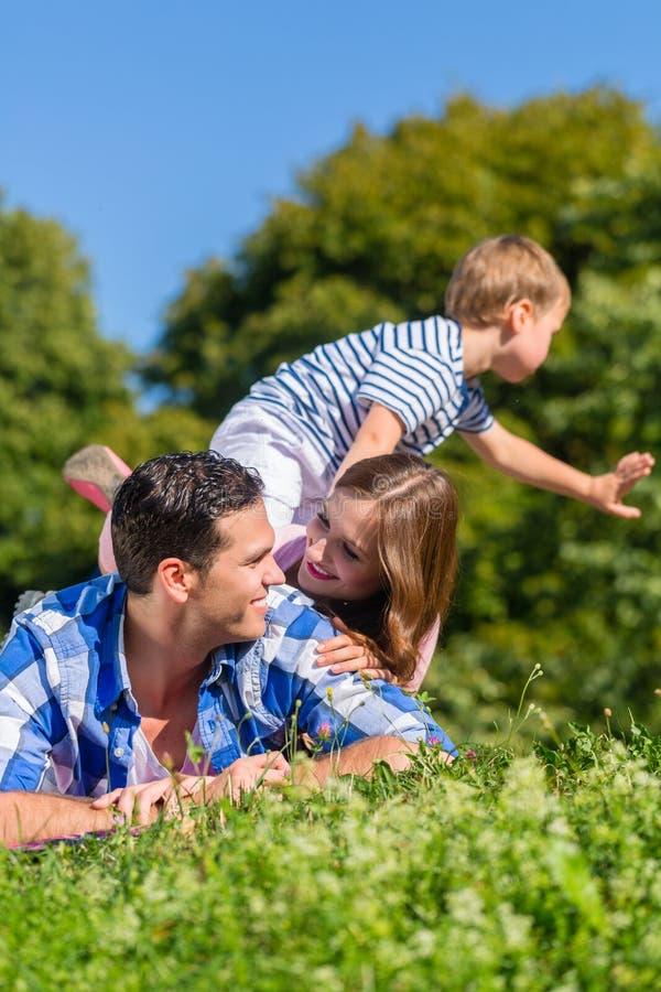 Семья лежа в траве na górze одина другого стоковая фотография