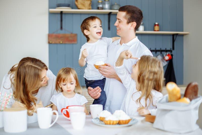 Семья есть завтрак в кухне их дома стоковые фото