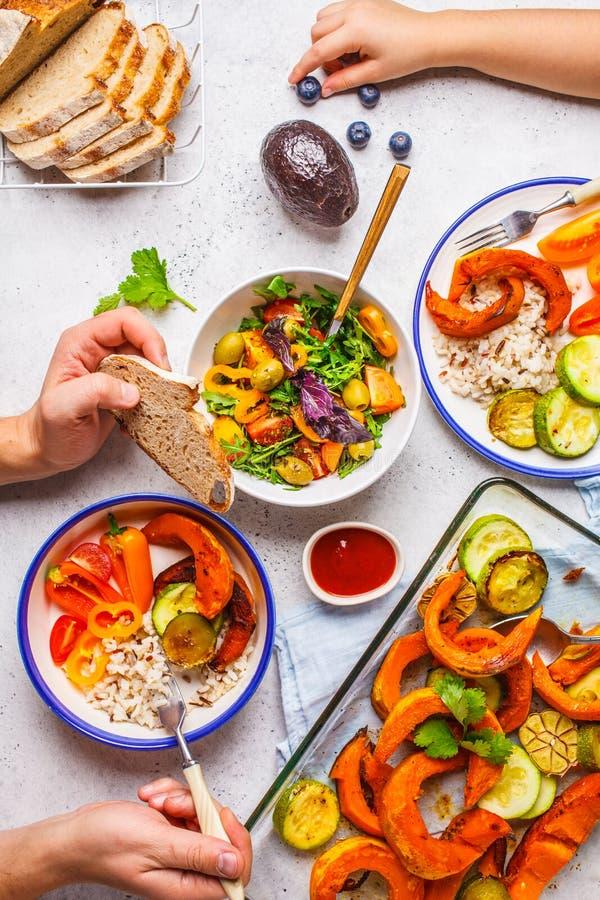 Семья есть здоровую вегетарианскую еду Взгляд столешницы обеда Vegan, завод основал диету Испеченные овощи, свежий салат, ягоды, стоковые изображения