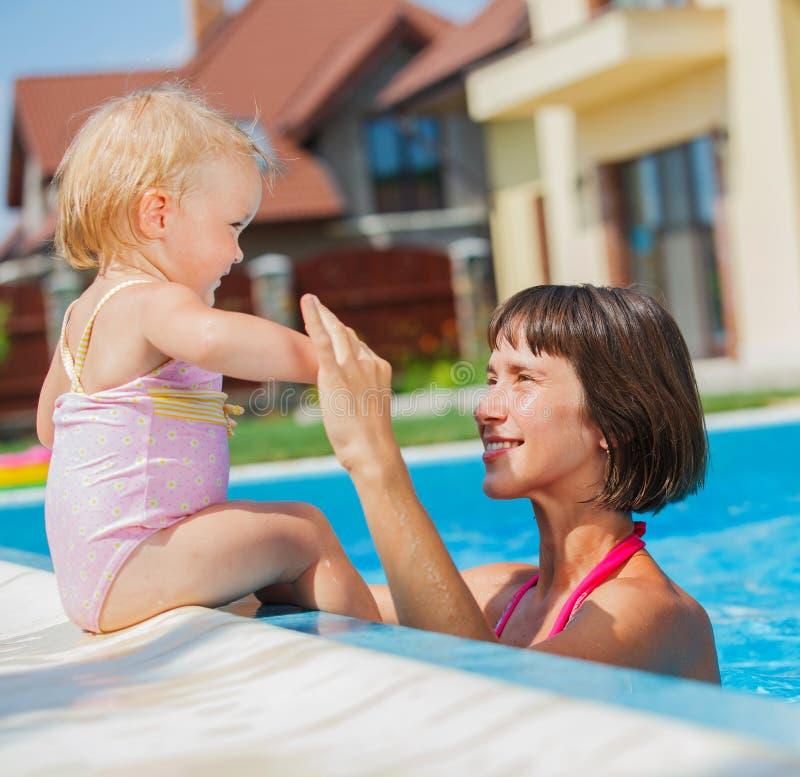 Семья играя в бассейне. стоковое фото rf