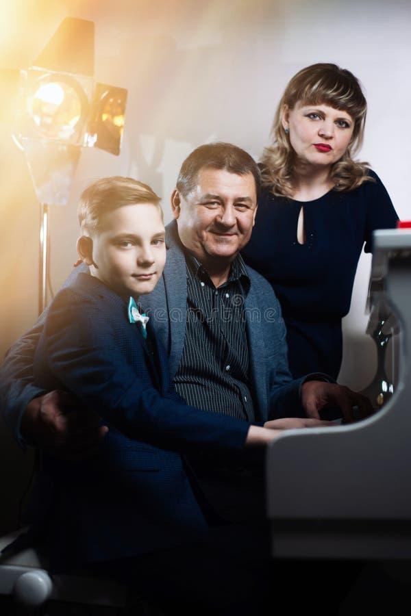 Семья играя на рояле Отец и мать учат, что сын играет музыкальный инструмент стоковые изображения rf