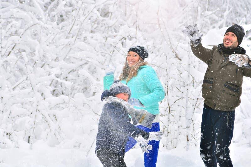 Семья играя снежные комья outdoors стоковые изображения rf