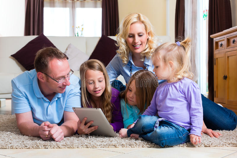 Семья играя с компьютером таблетки дома стоковая фотография
