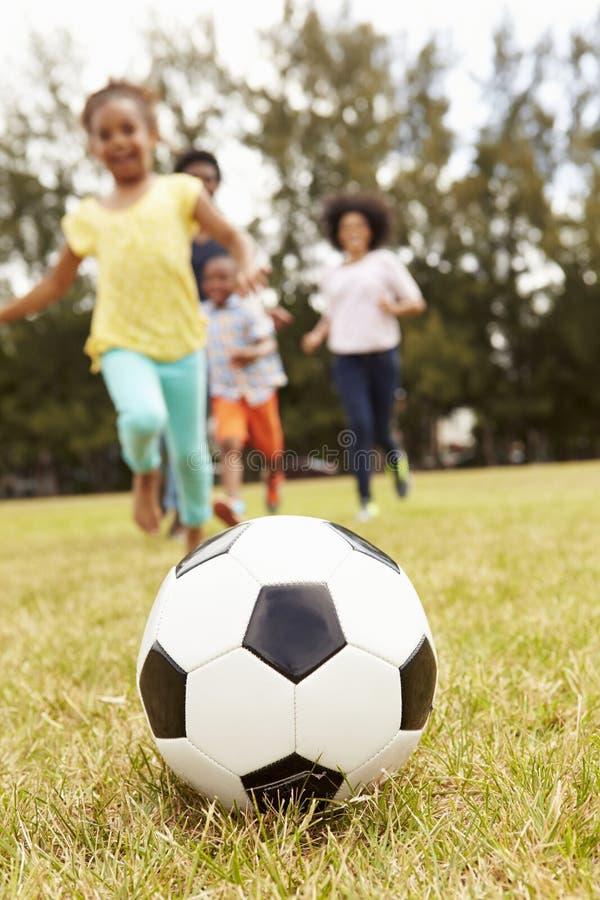 Семья играя футбол в парке совместно стоковая фотография