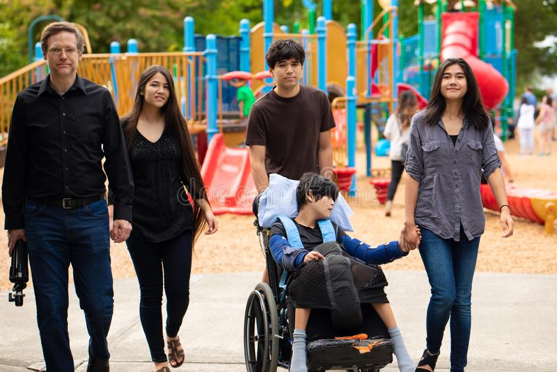 Семья идя за спортивной площадкой с неработающим сыном в кресло-коляске стоковые фото