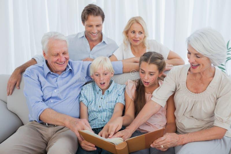 Семья из нескольких поколений смотря их фото альбома стоковая фотография