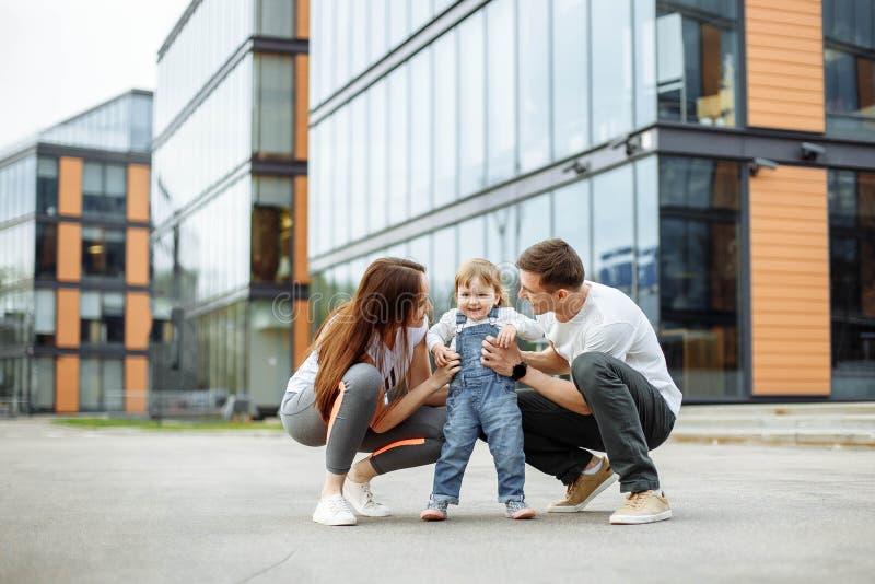 Семья из трех человек портрета счастливая Играть молодых родителей усмехаясь с их маленькой дочерью пока идущ через улицы  стоковое фото rf