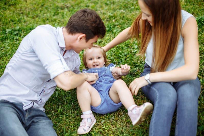 Семья из трех человек портрета счастливая Молодые родители играют при их маленькая дочь сидя на лужайке в парке стоковое изображение rf