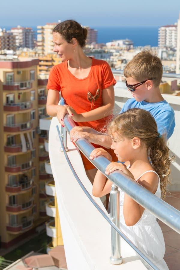 Семья из трех человек на балконе комнаты стоковая фотография rf