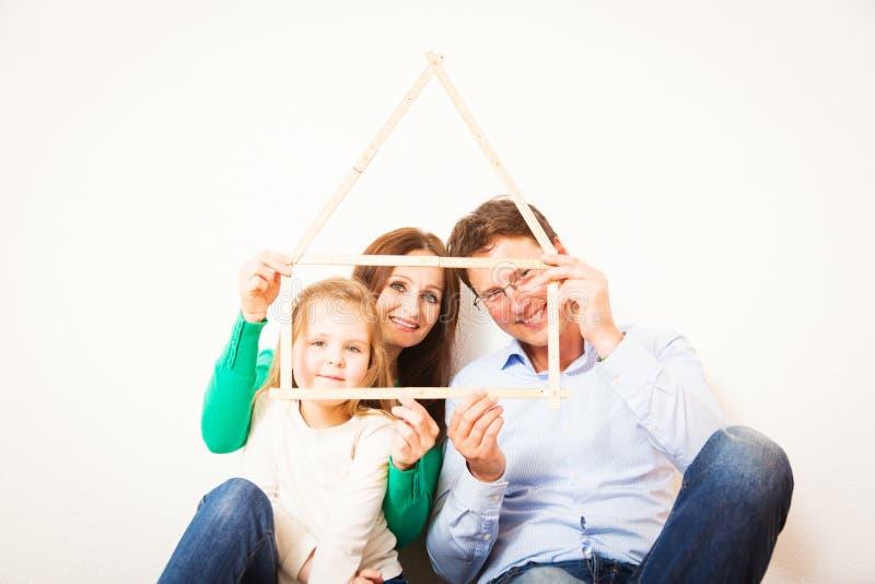Семья из трех человек с формой дома стоковые изображения