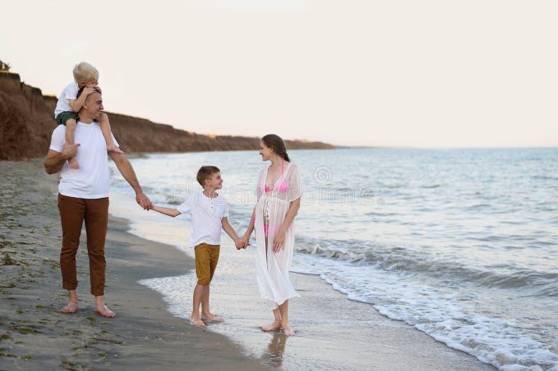 Семья из четырех человек идя вдоль seashore Родители и 2 сынов Счастливая дружелюбная семья стоковые изображения