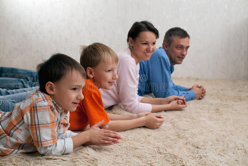Семья из четырех человек лежа на ковре стоковые фотографии rf