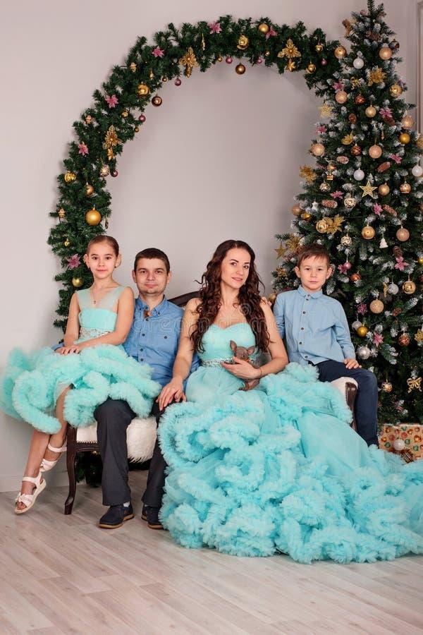 Семья из четырех человек с мальчиком и девушка в элегантных костюмах и платьях сидят на банкете около дерева Нового Года стоковые изображения