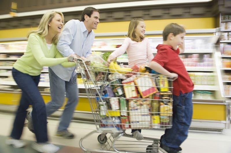 Семья из четырех человек бежать с полной вагонеткой покупок стоковые изображения rf