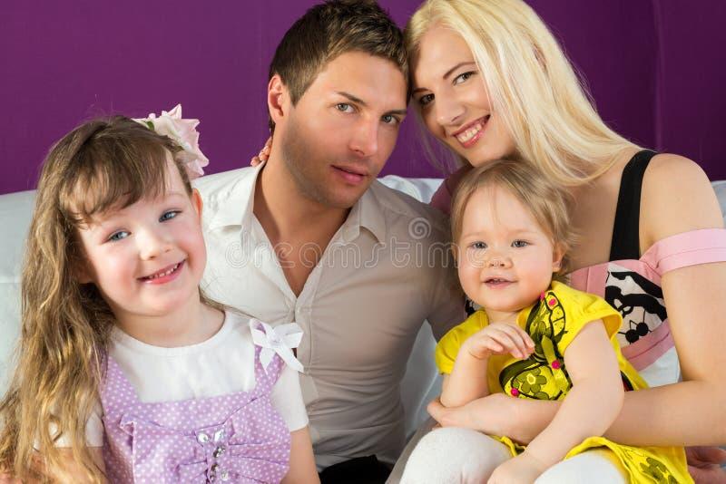 Семья из четырех человек в фиолетовой комнате стоковая фотография rf