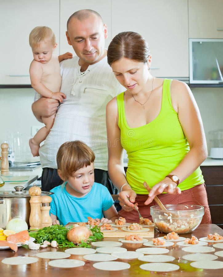 Семья из четырех человек делая вареники стоковое фото