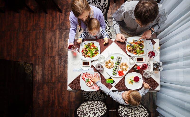 Семья из четырех человек имея еду на ресторане стоковые изображения