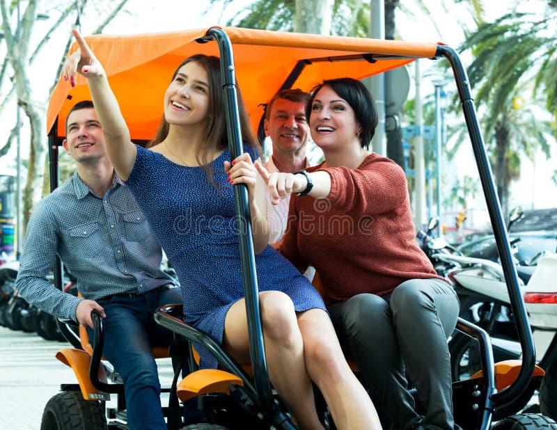 Семья из четырех человек сидя в грандиозном путешествии электрическом стоковые фото