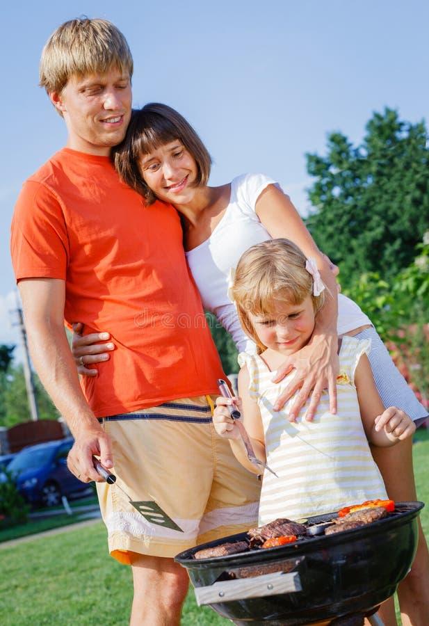 Семья имея барбекю outdoors стоковые изображения rf