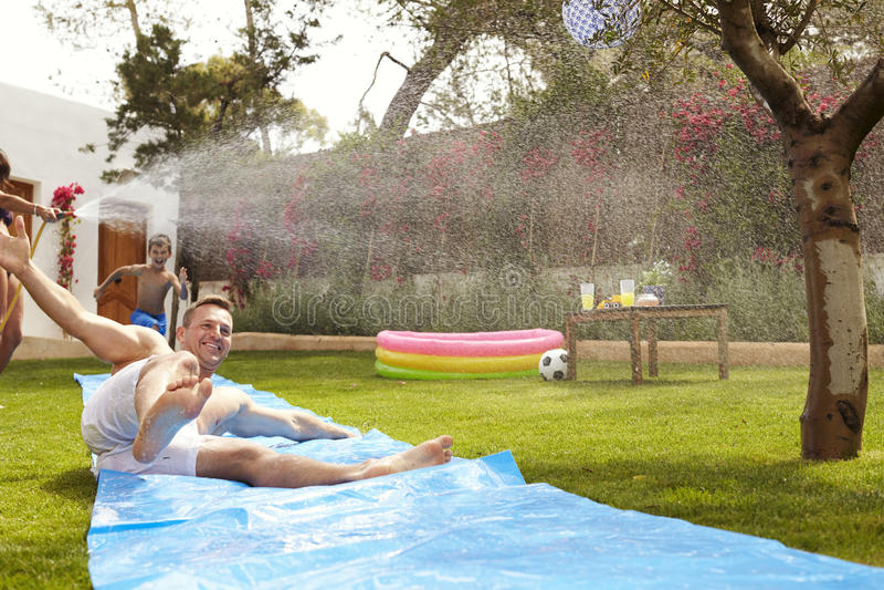 Семья имея потеху на водных горках в саде стоковая фотография rf