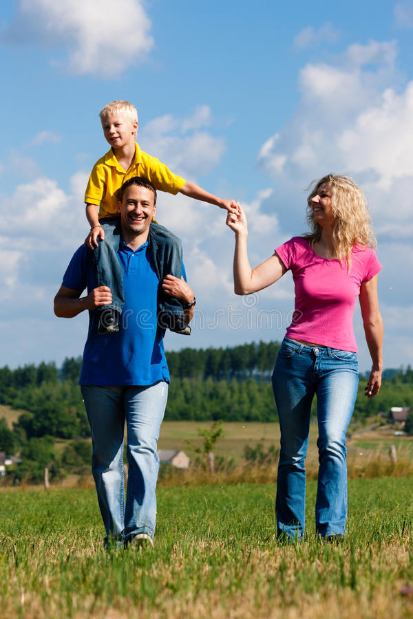 семья имея прогулку лужка стоковая фотография