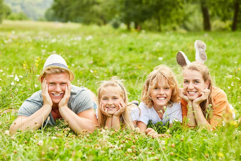 Семья и дети лежат на луге стоковое фото rf