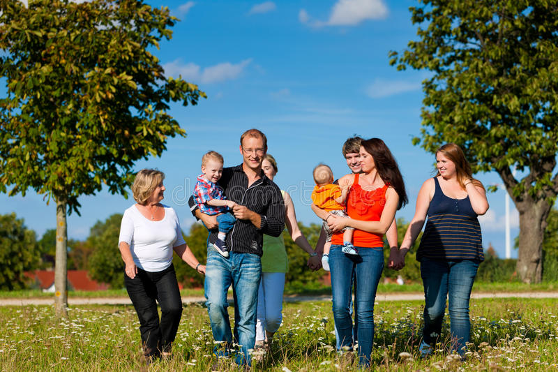 Семья и мульти-поколение - потеха на луге в лете стоковая фотография