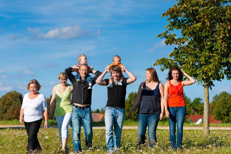 Семья и мульти-поколение - потеха на лужке в лете стоковое фото
