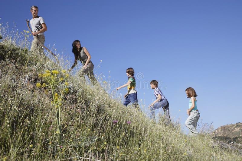 Семья идя вверх по наклону травы стоковая фотография rf