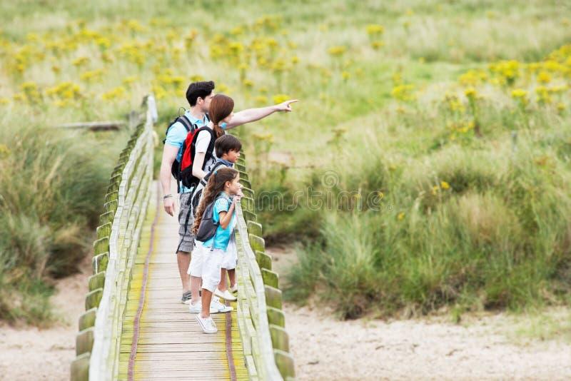 Семья идя вдоль деревянного моста стоковое изображение