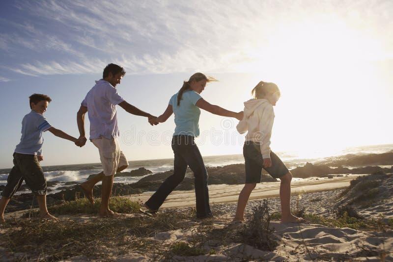 Семья идя рука об руку на пляж стоковое изображение