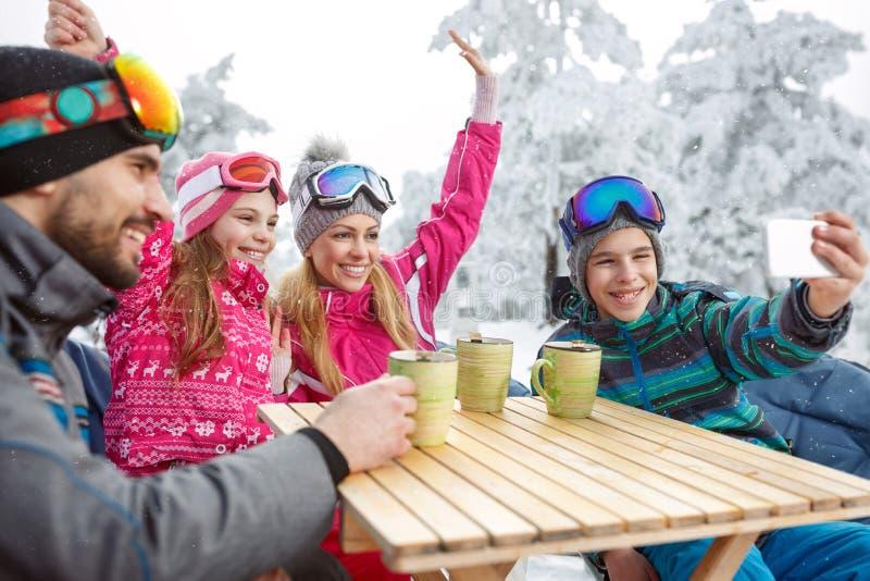 Семья катания на лыжах в кафе делая фото пока отдыхающ стоковая фотография