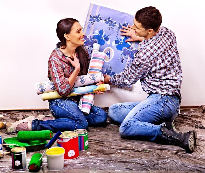 Семья клеит обои дома. стоковая фотография