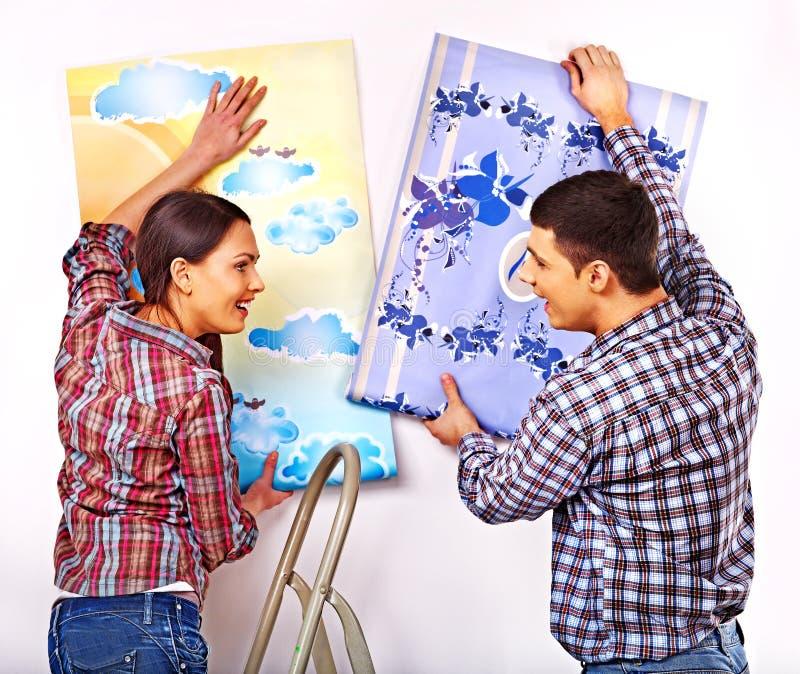 Семья клеит обои дома стоковое изображение rf