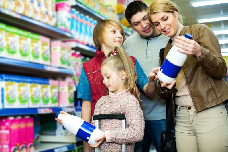 Семья клиентов при дети покупая молоко стоковая фотография rf