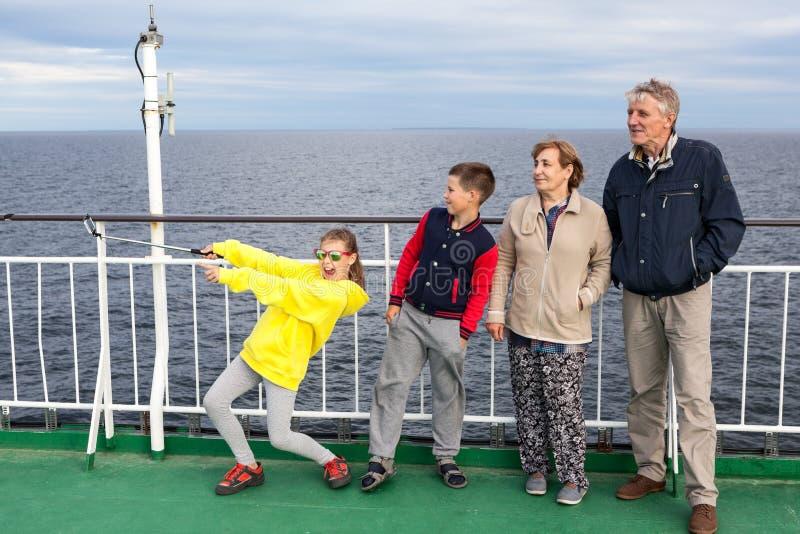 Семья 4 людей принимая selfie с ручкой, имеющ отключение на пароме круиза, дедов моря с внуками стоковое изображение rf